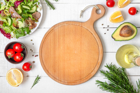 Mockup with empty wood cutting board. Fresh salad and ingredients for cooking on white wooden background. Food background with copy space.