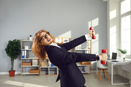 Busy office worker trying to have sports workout at work. Funny nerdy man in business suit exercising with dumbbells during workday. Fitness training, hectic life, corporate wellness program concept