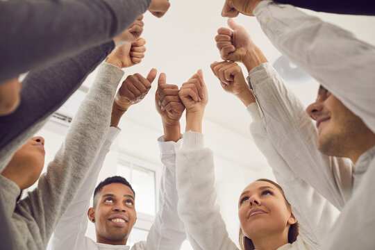 Business concept. Team of happy friends celebrating teamwork and success in group meeting. Low angle of young people joining hands and giving thumbs-up, all together voting for good idea or suggestion