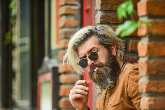 Went on smoke break. Hipster smoking irish pub entrance background. Smoking habit. Brutal guy sunglasses smoking tobacco. Smoking outdoors. Fashionable mature man with cigarette. Cool guy relaxing