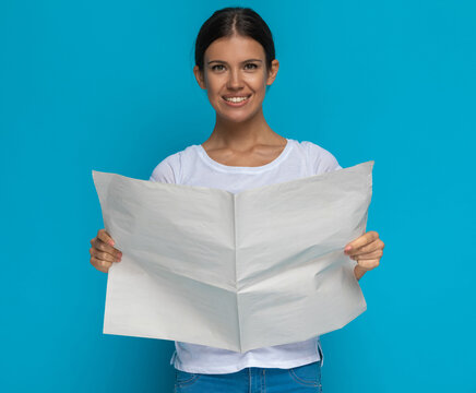 attractive casual woman reading her newspaper and smiling