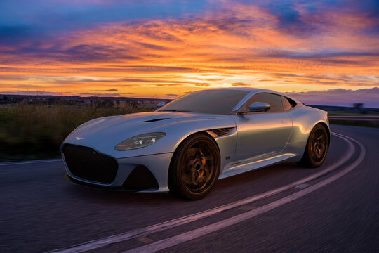 Aston Martin DBS superleggera on a scenic road at sunset.
