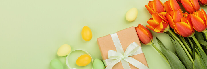 Stylish background with colorful easter eggs pastel colors isolated on green background. Horizontal...