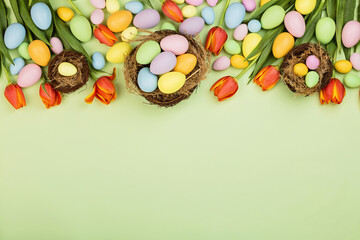 Stylish background with colorful easter eggs pastel colors isolated on green background. Flat lay,...