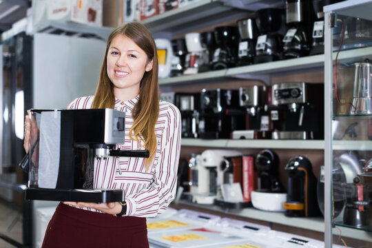 Positive saleswoman suggesting coffee brewer in shop of kitchen appliances