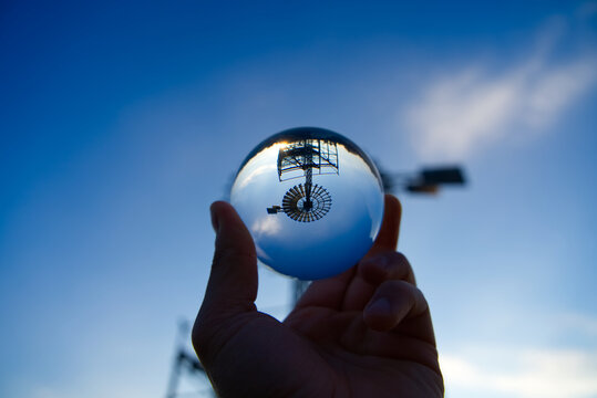 Cropped Hand Of Man Holding Crystal Ball With Reflection Of Windmill Against Blue Sky
