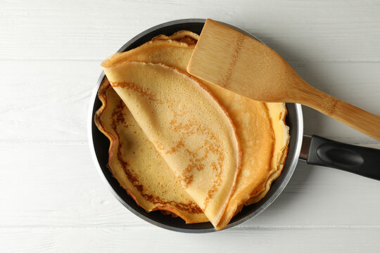 Pan with tasty thin pancakes and spatula on wooden table