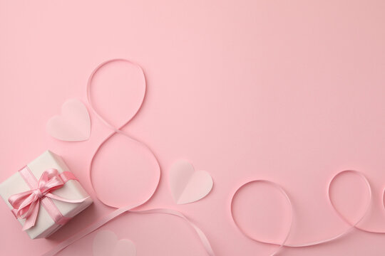 8 made of ribbon, hearts and gift box on pink background