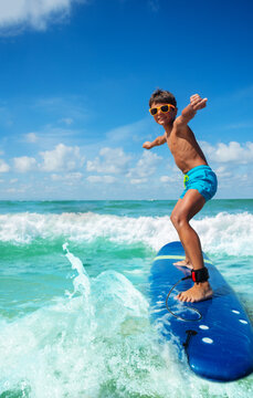 Photo of a boy riding surfboard on the small sea waves practicing with his board in cute sunglasses