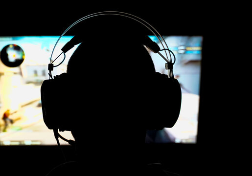 Silhouette of a person playing a 3D shooter game on a computer in a dark room. Shallow depth of field.