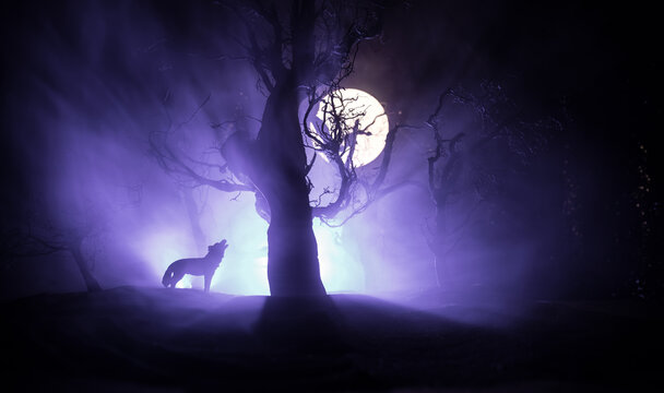 Silhouette of howling wolf against dead forest skyline and full moon. Creative artwork decoration.