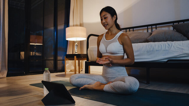 Young Asia lady in sportswear exercises doing work out and using tablet to watch yoga video tutorial at home night. Distant training with personal trainer, social distance, online education concept.