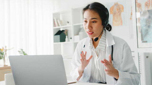 Young Asia lady doctor in white medical uniform with stethoscope using computer laptop talking video conference call with patient at desk in health clinic or hospital. Consulting and therapy concept.