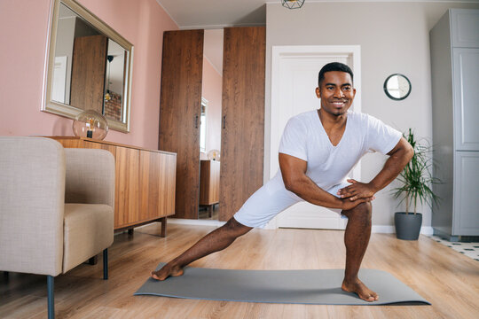 Front view of cheerful African-American man doing side lunge exercise at home during working out standing on yoga mat at bright domestic room, looking at camera . Concept of sport training at home gym
