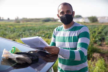 Portrait of male farmer wearing protective face mask signing documents near car outside