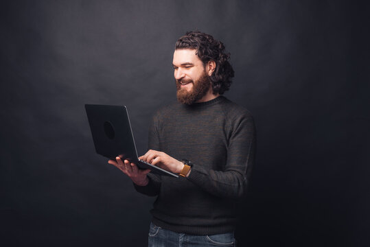 Portrait of handsome man in casual using laptop over black background.