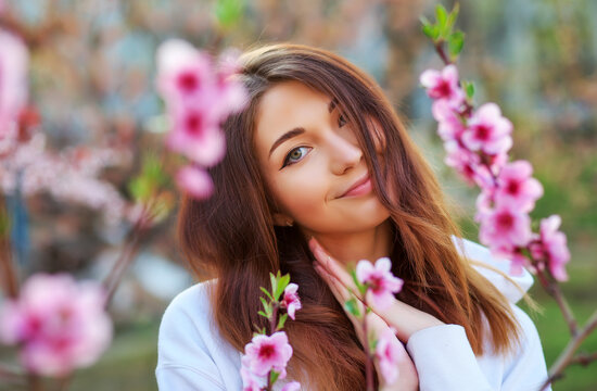 Smiling beautiful girl standing near a peach tree during sunset. Happy face. Spring time.
