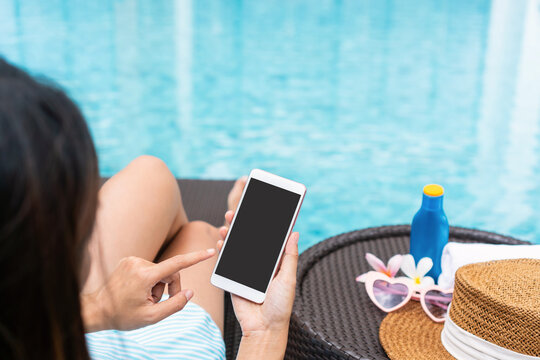 Happy Asian girl wearing swimsuit lying on sunbed and using smart phone relaxing at the poolside with hat, towel, mobile phone and sun cream. Summer, holiday and vacation concept. Copy space, close up