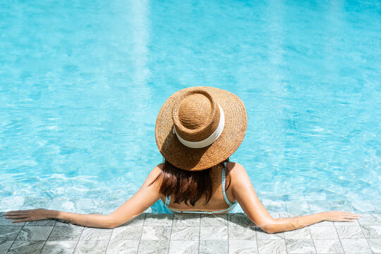 Rear view of attractive Asian woman in bikini and straw hat relaxing in luxury swimming pool