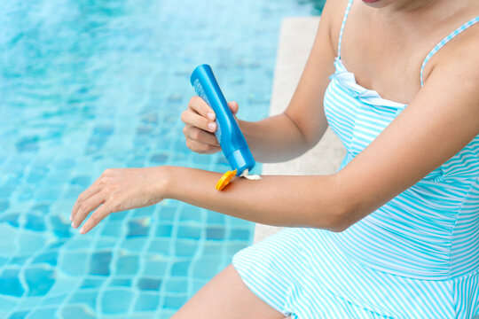 Happy Asian girl in one piece swimsuit applying sun cream or UV protection cream on to her arm before swimming. Sunburn protection. Summer holidays and vacation concept.