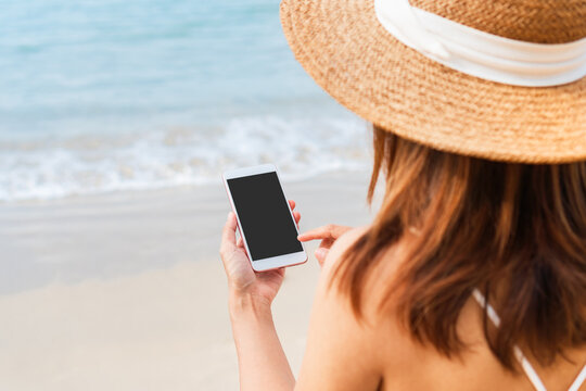 Happy traveler Asian woman in white dress using mobile phone at tropical beach. Summer, holiday, technology and lifestyle concept.