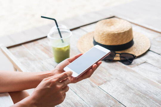 Hands of Asian woman using mobile phone with iced Matcha latte, hat, sunglasses on wooden table in cafe. Closeup. relax on weekend concept.