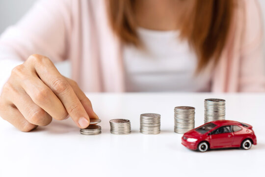 Close up of hand putting coin on pile coins for saving money. Collect money to buy a new car, savings and car loan concept. Flat lay