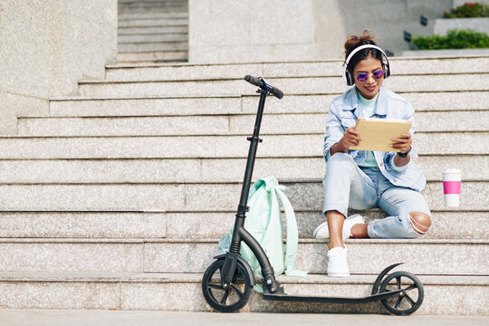 Happy young pretty woman sitting on steps after riding on electric scooter on campus and watching webinar on table computer
