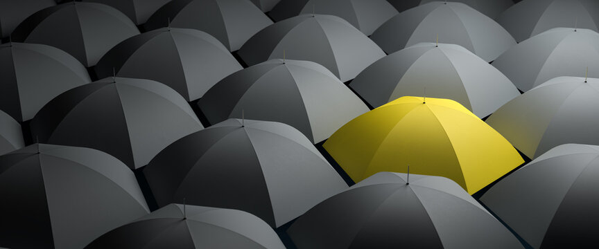 Color of the year 2021 - Standing out from the crowd concept. A yellow umbrella within a sea of gray umbrellas.