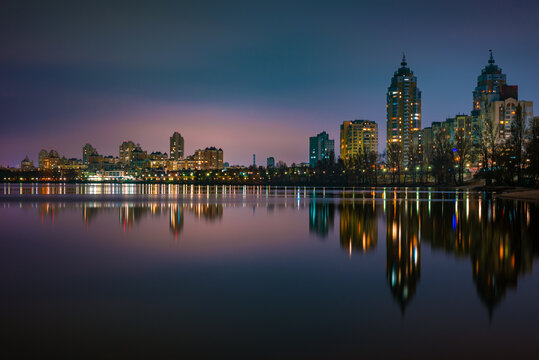 Night view of modern buildings in the Obolon district of Kiev, Ukraine, close to the Dnieper River, The lights reflect on the calm water.