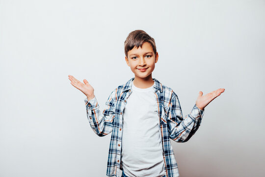 Portrait confident Boy shirt happy positive smile hold two Hands balance compare product offer isolated over gray background. young child boy pointing at something big