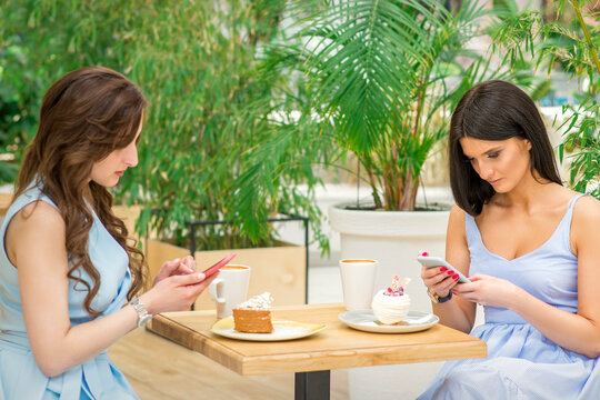 Two young women looking their smartphones while sitting in a cafe. Technology people addictions