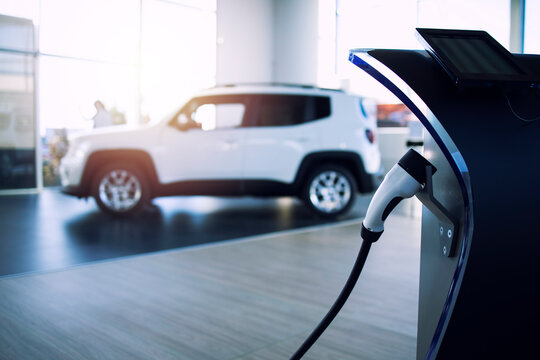 Car dealership selling electric car and charger in showroom.