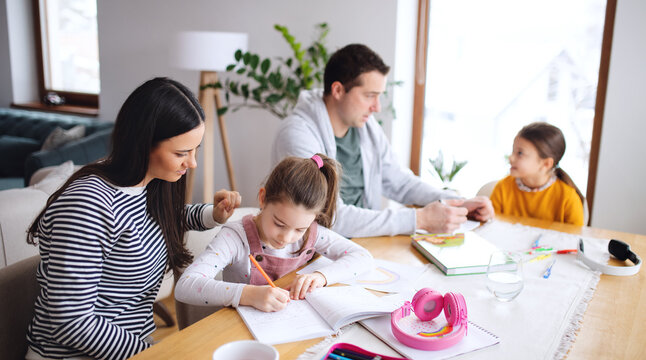 Parents with school girls indoors at home, distance learning.