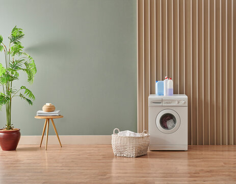 Washing machine in the green and wooden wall style with dirty clothes, laundry room style with detergent.