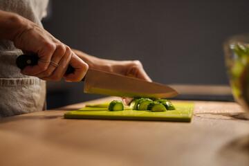 Caucasian woman wearing apron cutting cucumber at home kitchen - fototapety na wymiar