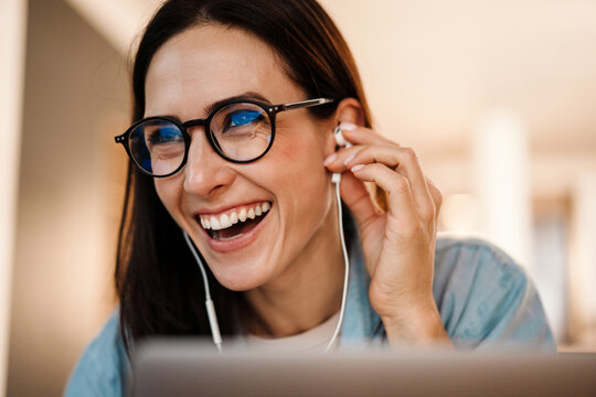 Happy beautiful woman in earphones laughing while using laptop