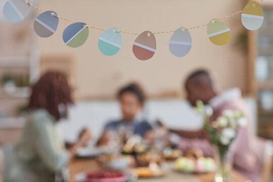 Background image of Easter decorations shaped as Easter eggs with blurred African-American family in background, copy space