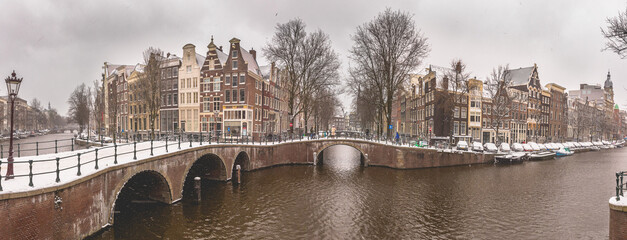 Winter snow view of Dutch canal and old houses in the historic city of Amsterdam, the Netherlands
