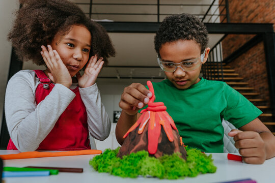 Children making DIY volcano model from kids play clay