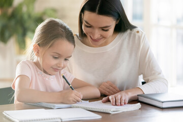 Smiling young mother and little 7s daughter study at home write make homework together. Happy...