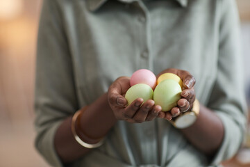 Close up of unrecognizable African-American woman holding pastel colored easter eggs , focus on...