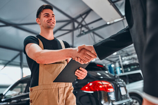 Businessman customer shaking hands with the mechanic in the auto repair shop.