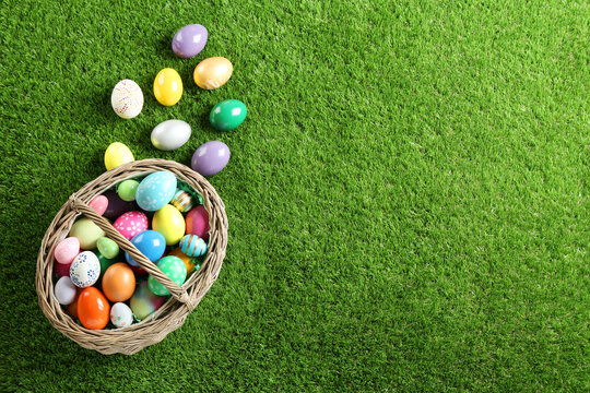 Wicker basket with Easter eggs on green grass, flat lay. Space for text