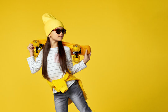 cool hipster little child girl in sunglasses posing with yellow skateboard on studio background. copy space
