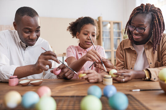 Portrait of happy African-American family painting Easter eggs together while sitting at wooden table in cozy home interior, DIY Easter decorations