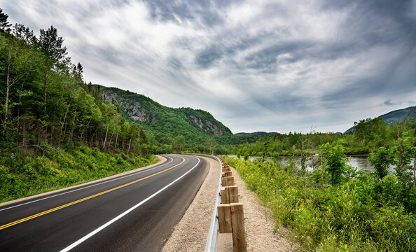 Canadian road in Quebec Province meandering  between river and and cliffs with trees everywhere at summer time during a cloudy day