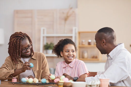 Portrait of laughing African-American family painting Easter eggs together while sitting at wooden table in cozy home interior and enjoying DIY art