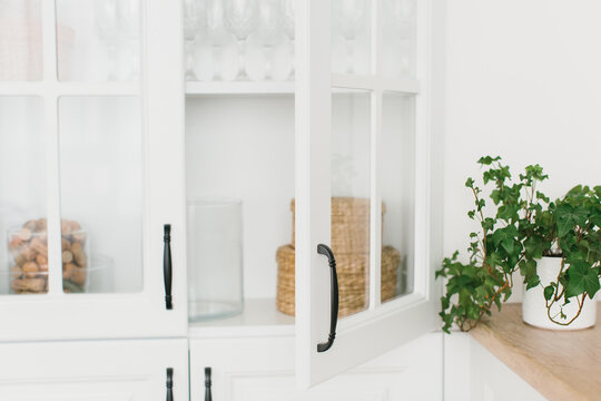 Opened door of white glass cabinet with clean dishes and decor. Scandinavian style kitchen interior. Organization of storage in kitchen. Selective focus.