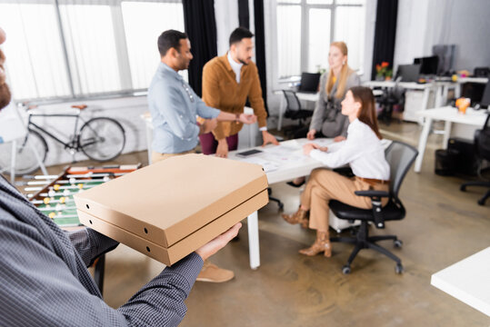 Delivery man holding pizza boxes near business people on blurred background in office